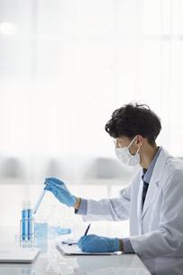 白い空間で実験をしている白衣を着た男性の写真素材 [FYI04573815]