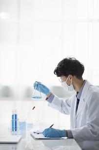 白い空間で実験をしている白衣を着た男性の写真素材 [FYI04573816]