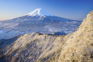 山梨県 雪景色の稜線越しに見える富士山の写真素材 [FYI04573832]