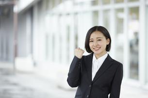 ガッツポーズして微笑むリクルートスーツの女性の写真素材 [FYI04574193]