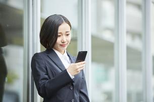 スマートフォンを操作するリクルートスーツを着た女性の写真素材 [FYI04574195]