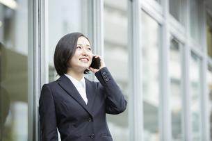 笑顔で電話をするリクルートスーツの女性の写真素材 [FYI04574198]