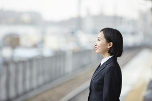 駅のホームで微笑むスーツ姿の女性の横顔の写真素材 [FYI04574199]