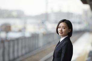 駅のホームで微笑むスーツ姿の女性の写真素材 [FYI04574200]