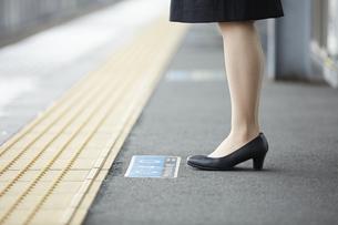 駅のホームに立つスーツ姿の女性の足下の写真素材 [FYI04574205]