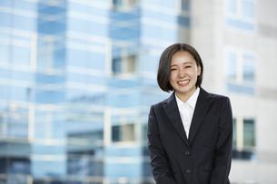ビル の背景とリクルートスーツを着た笑顔の女性の写真素材 [FYI04574210]