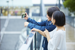 スマートフォンで自撮りをするカップルの写真素材 [FYI04574225]