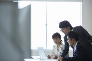 一つのノートパソコンを眺める3人の働く人達の写真素材 [FYI04574241]
