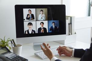 リモート会議中のパソコンと男性の手の写真素材 [FYI04574255]