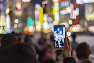 東京都 渋谷センター街の夜景とスマートフォンの写真素材 [FYI04574356]