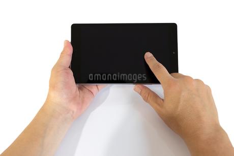 タブレットの画面をタップする中年男性の手の写真素材 [FYI04575926]