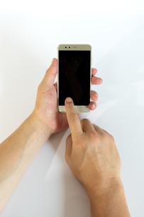 スマートフォンの画面をタップする中年男性の手の写真素材 [FYI04575929]