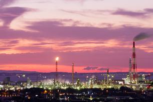 朝焼けに染まる空と工場の光の写真素材 [FYI04576129]