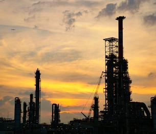 夕焼けの空を背景にした四日市コンビナートのシルエットの写真素材 [FYI04576139]