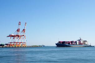 四日市港の霞岸壁に接岸しようとするコンテナ船とコンテナクレーンの写真素材 [FYI04576142]