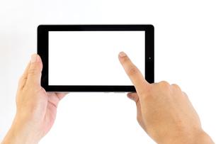 タブレットの画面右側をタップする中年男性の手の写真素材 [FYI04576746]