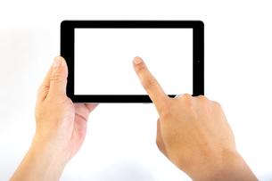 タブレットの画面中央をタップする中年男性の手の写真素材 [FYI04576747]