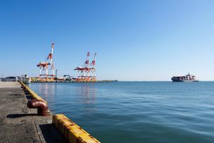 四日市港の霞岸壁に接岸しようとするコンテナ船とコンテナクレーンの写真素材 [FYI04576851]