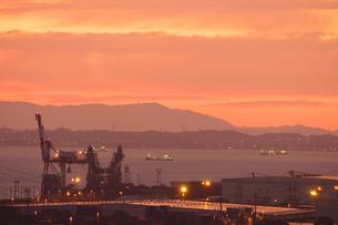 朝焼けに染まる四日市港のコンテナクレーンの写真素材 [FYI04576857]