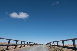 美ヶ原高原の柵が続く砂利道。澄んだ青空に雲が1つ浮かぶの写真素材 [FYI04576859]