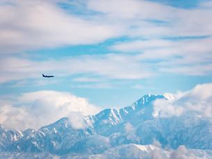 雪が積もった冬の北アルプス立山連峰と着陸前の飛行機の写真素材 [FYI04577957]
