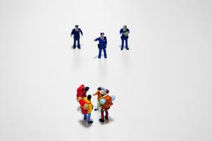 ニューノーマルに従わない密集した外出者を注意する警察官の写真素材 [FYI04578984]