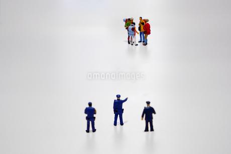 ニューノーマルに従わない密集した外出者を注意する警察官の写真素材 [FYI04578985]