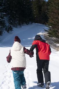 手をつないで雪の上を歩くカップルの写真素材 [FYI04579085]