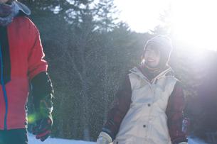 雪の上で微笑むスノーウェアの女性の写真素材 [FYI04579112]