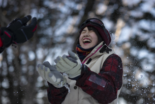 雪遊びをするスノーウェアの女性の写真素材 [FYI04579124]