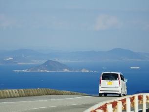 伊勢志摩スカイラインから見える海と島々と疾走する軽自動車の写真素材 [FYI04579621]