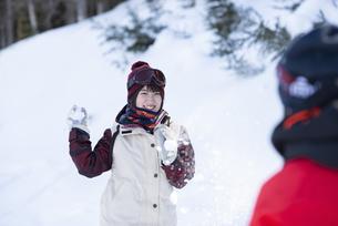 雪玉を投げる女性の写真素材 [FYI04579881]
