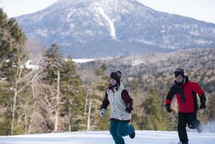 雪の上を走るカップルの写真素材 [FYI04579896]