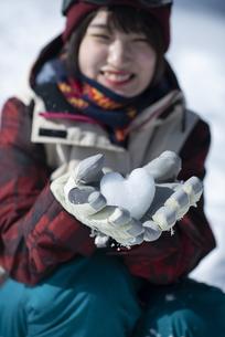 雪のハートを持つウィンターウェアの女性の写真素材 [FYI04579954]