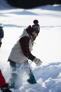 雪玉をぶつけるスノーウェアの女性の写真素材 [FYI04579978]