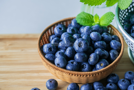 Fresh ripe blueberries in basket on wooden background.の写真素材 [FYI04580067]