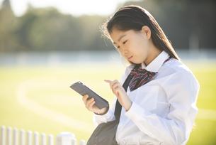 公園でスマホを見ている制服姿の女子学生の写真素材 [FYI04580115]