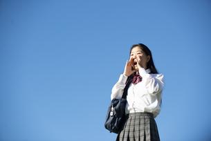 口元に手を当てて叫んでいる制服姿の女子学生の写真素材 [FYI04580191]