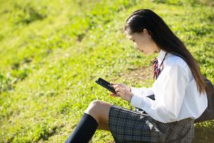 芝生に座ってスマホを見ている制服姿の女子学生の写真素材 [FYI04580192]