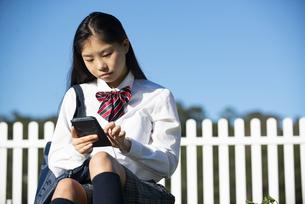 座ってスマホを見ている制服姿の女子学生の写真素材 [FYI04580193]