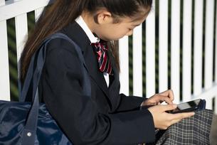 スマホを見ている制服姿の女子学生の写真素材 [FYI04580209]