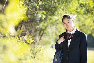 緑の中にいる制服姿の女子学生の写真素材 [FYI04580255]
