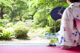 縁側に座る浴衣の女性と金魚鉢の写真素材 [FYI04581066]
