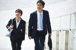 外を歩いているスーツを着た男性と女性の写真素材 [FYI04581221]