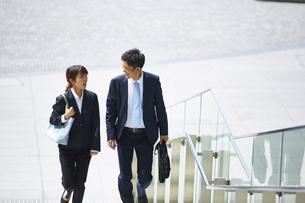 外を歩いているスーツを着た男性と女性の写真素材 [FYI04581222]