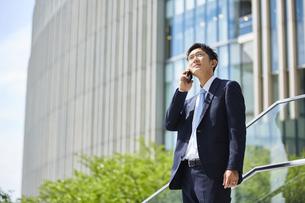 スマートフォンで通話をしているスーツを着た男性の写真素材 [FYI04581223]