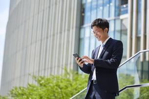 スマートフォンを見ているスーツを着た男性の写真素材 [FYI04581224]