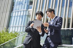 外で会話しているスーツを着た二人の男性の写真素材 [FYI04581228]