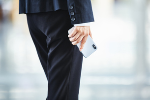 スマートフォンを持っているスーツを着た女性の写真素材 [FYI04581235]