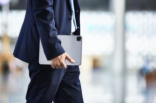 タブレット端末を持っているスーツを着た男性の写真素材 [FYI04581236]